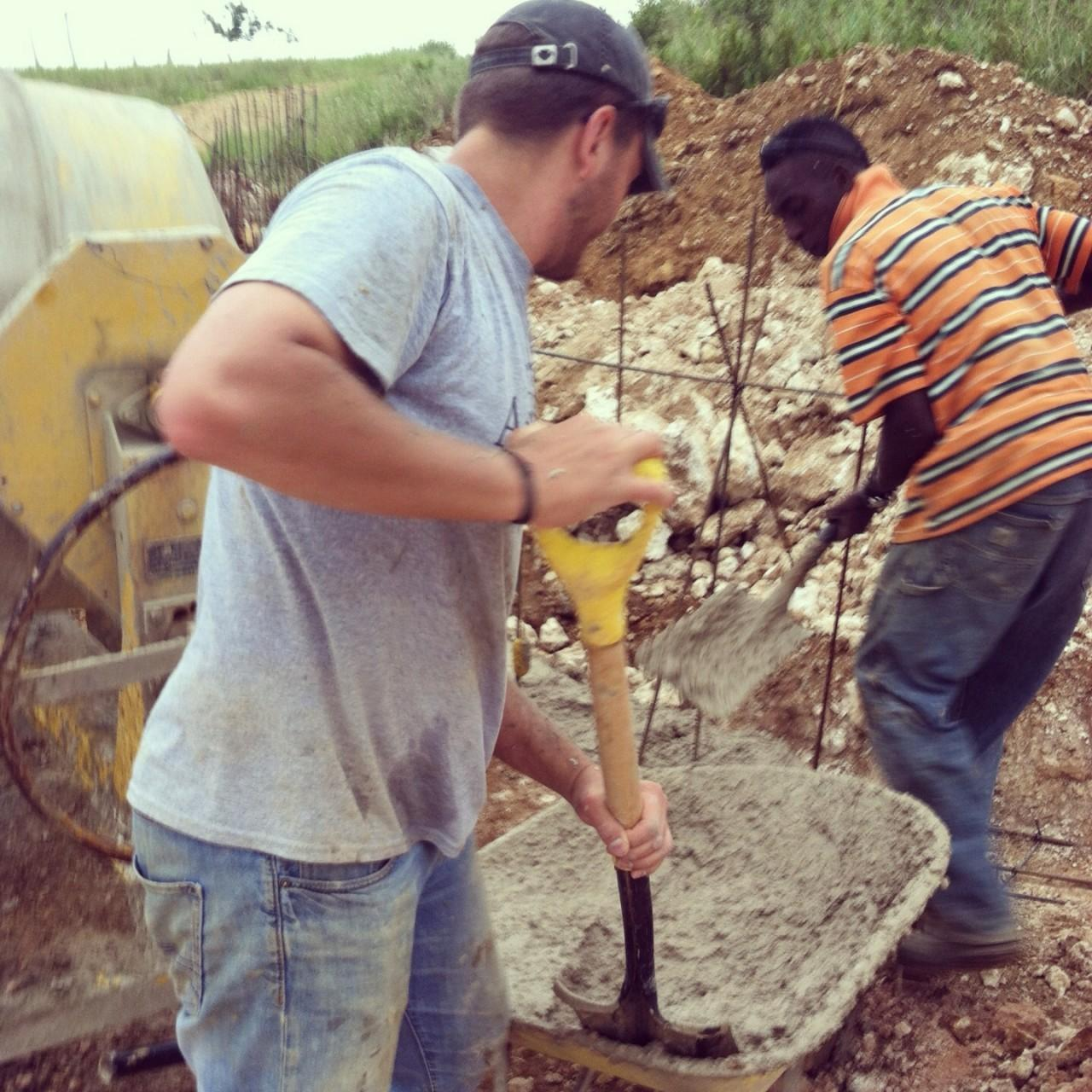 Two men shoveling cement.